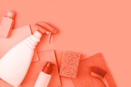 House cleaning products are on coral background. Cleaning concept.