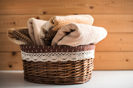 Kosz z miękkimi ręcznikami kąpielowymi na drewnianym tle.