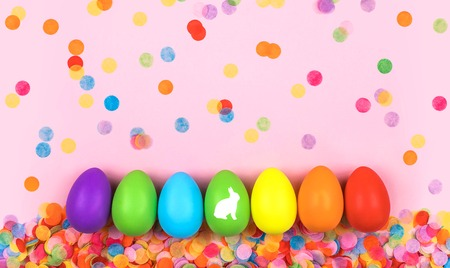 Colored Easter eggs on pink background with confetti. Flat lay.