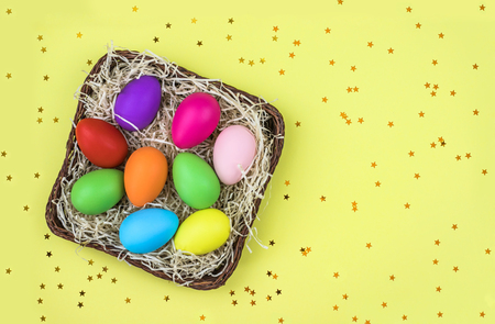 Colored Easter eggs in the basket on yellow background with golden confetti. Flat lay.