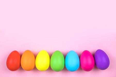Uova di Pasqua colorate su sfondo rosa con paglia. Disposizione piatta.