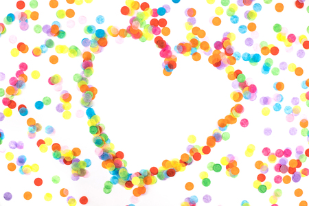 Bright multicolored confetti in the shape of heart isolated on a white background. Festive concept. Childrens party, birthday, wedding, celebration. Top view. Copy space. Imagens - 124894492