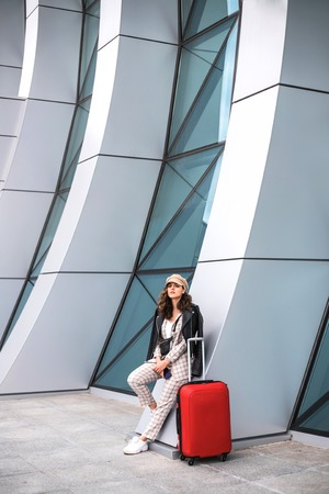 Beautiful businesswoman with red suitcase near the backdrop of the airport.