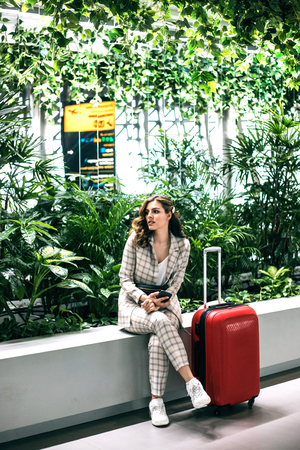 Young beautiful businesswoman with luggage in Airport waiting room talking by phone. Stock Photo