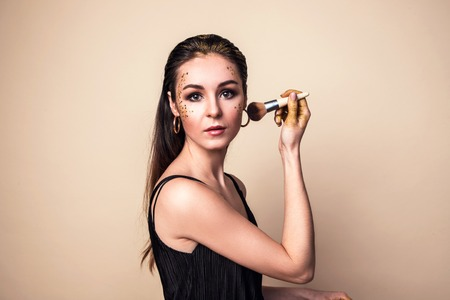 Attractive young woman with glitter make-up getting powder on her cheek with a brush. She posing at camera in the studio.