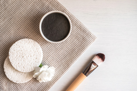 Preparing natural cosmetic facial mask in ceramic bowl on white wooden background with brush and flower. Rustic style.