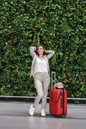 Young beautiful businesswoman with luggage in Airport against big green wall from natural plants. She is happy to arrive.