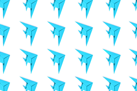 Pattern of blue paper origami fishes isolated on white background.