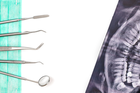 Dentist tools on mask and x-ray photo isolated on white background. Flat lay. Stock Photo