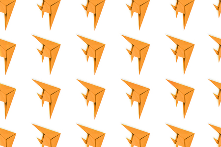 Pattern of turmeric paper origami fishes isolated on white background.