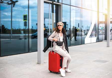 Beautiful businesswoman with red suitcase against the backdrop of the airport.