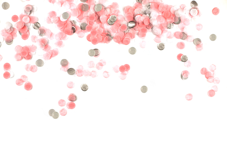 Delicate pink and silver confetti isolated on a white background. Festive concept. Childrens party, birthday, wedding, celebration. Top view. Copy space. Stock Photo
