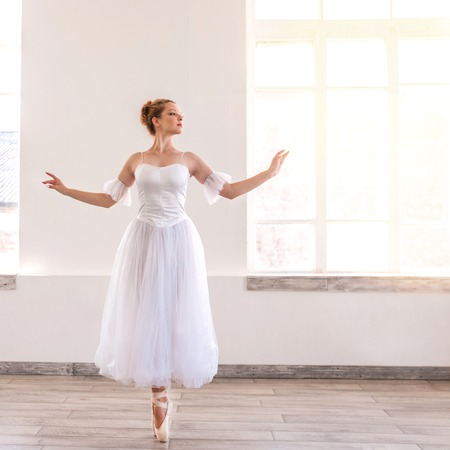 Young graceful ballerina dancing on white studio. Beautiful dancer is training.