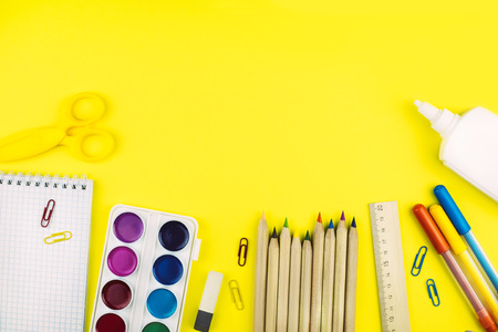 Different school supplies on bright yellow paper background. Back to school background. Flat lay, copy space. Imagens - 124894843