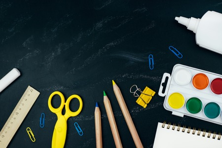 Different school supplies on black chalkboard background. Back to school background. Flat lay, copy space. Banco de Imagens