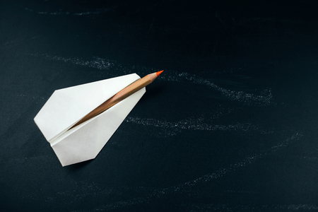 White paper airplane with crayon on black chalkboard. Education and motivation concept. Reach your goal and be first.