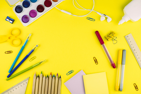 Different school supplies on bright yellow paper background. Back to school background. Flat lay, copy space. Banco de Imagens