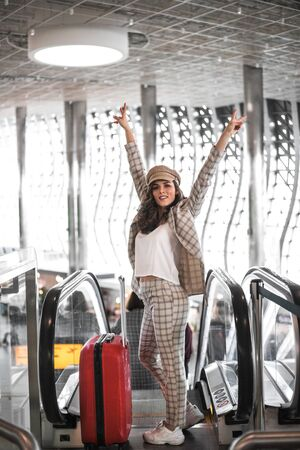 Beautiful business woman on escalator in airport holding thumbs up. Job and travel concept 写真素材