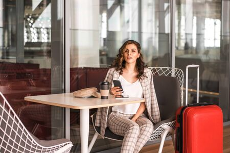 Beautiful business woman with smartphone waiting for her flight in an airports cafe.