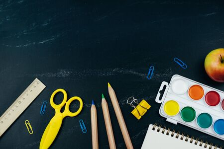 Different school supplies on blackboard background. Back to school background. Flat lay, copy space. Imagens - 124895024