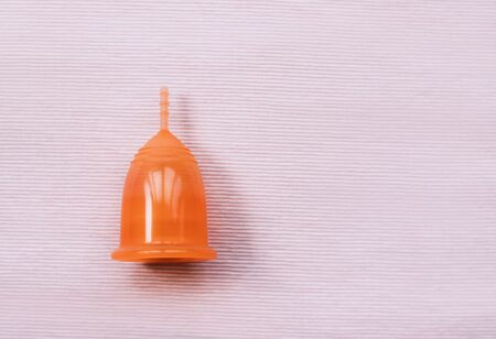Orange menstrual cup on a pink background. Close up.