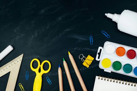 Different school supplies on blackboard background. Back to school background. Flat lay, copy space.