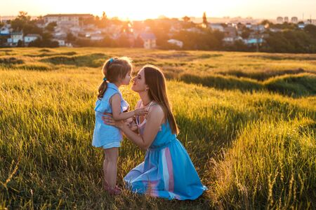 Young mother and daughter, hugging and playing in a golden field of sunshine while on a summer holiday. Family activities and outdoors concept. 版權商用圖片
