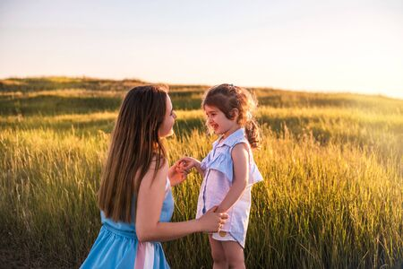 Young mother and daughter, hugging and playing in a golden field of sunshine while on a summer holiday. Family activities and outdoors concept. Banque d'images