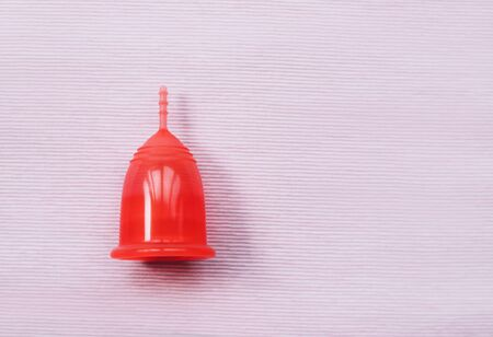 Red menstrual cup on a pink background. Close up.
