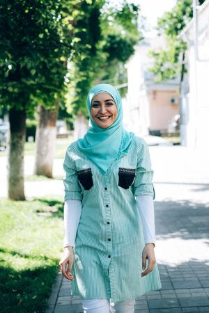 Portrait of pretty young muslim woman on a street. Woman in hijab laughing and looking at camera.