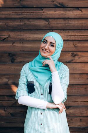 Portrait of pretty young muslim woman on a street. Woman in hijab smiling and looking at camera against wooden background.