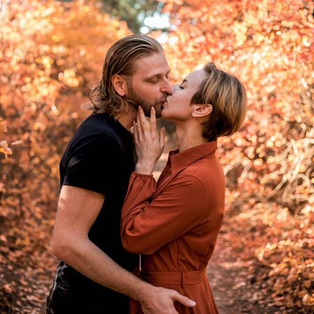 Beautiful young couple in love hugging and kissingg in the autumn forest. Reklamní fotografie - 130556873
