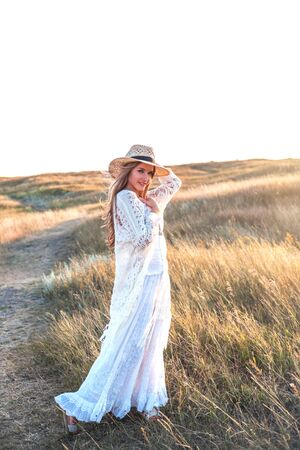 Beautiful woman wearing in white dress and straw hat enjoying nature outdoors at sunset.