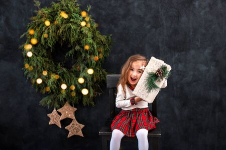 Happy little smiling girl with christmas gift box on the chair on the christmas tree background. Stock Photo