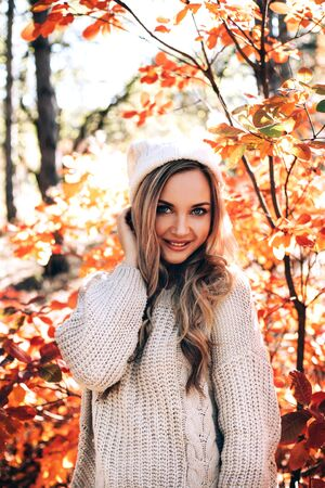 Beautiful smiling woman enjoying autumn in the forest. Banque d'images - 131958431