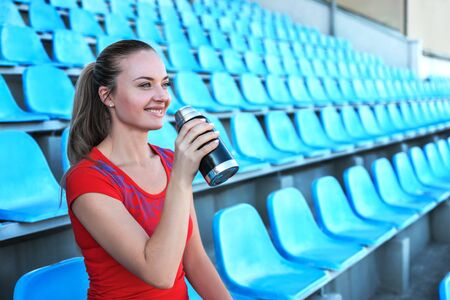 Beautiful sportswoman drinking water after work out at the stadium.