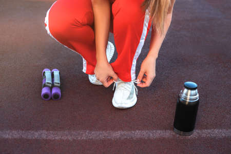 Young beautiful woman tying shoelaces on the stadium. flask with water and weights are near her legs.