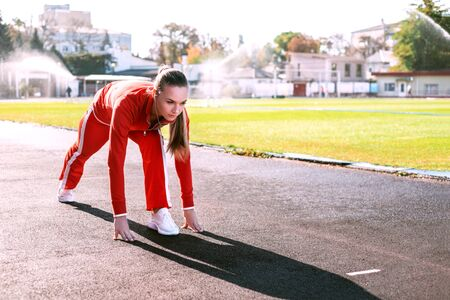 Beautiful girl in red tracksuit is ready to run on the sport stadium.