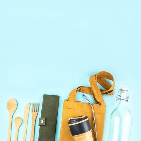 Eco bags with bamboo cutlery, reusable coffee mug and water bottle on blue background. Sustainable lifestyle. Zero waste and plastic free concept. Archivio Fotografico - 133484051