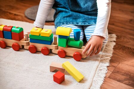 Little cute girl plays with wooden train. Toddler girl at day care.