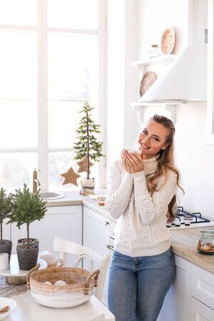 Beautiful young woman drink tea at the festive kitchen. Christmas and New year concept. Standard-Bild - 133941400