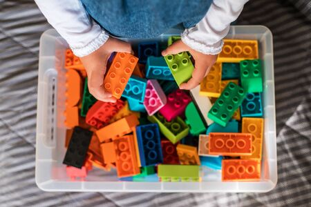 Little girl cleaning up the toy box at home. Childs space organization.
