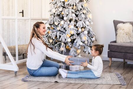 Happy mother and daughter seating with gift box over living room and christmas tree background.