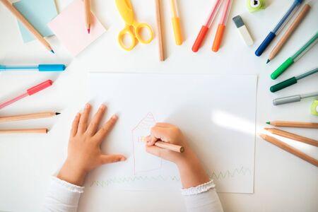 Nahaufnahme von Kinderhänden, die auf weißem Papier in bunten Stiften und Bleistiften zeichnen. Standard-Bild