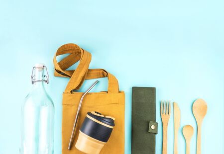 Eco bags with bamboo cutlery, reusable coffee mug and water bottle on blue background. Sustainable lifestyle. Zero waste and plastic free concept. Stock Photo