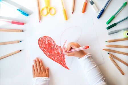 Close up of childs hands drawing red heart at white paper within colorful pens and pencils.