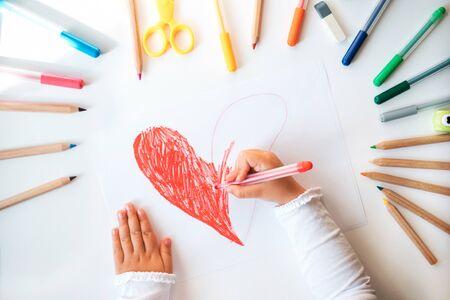 Nahaufnahme der Kinderhände, die rotes Herz auf weißem Papier in bunten Stiften und Bleistiften zeichnen. Standard-Bild