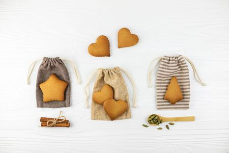 Heart shaped cookies, cinnamon and spoons with cardamon on cotton bags on white wooden background. Flat lay style.