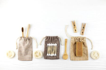 Set of eco natural bathroom accessories on white wooden background. Zero waste concept. Plastic free. Flat lay style.