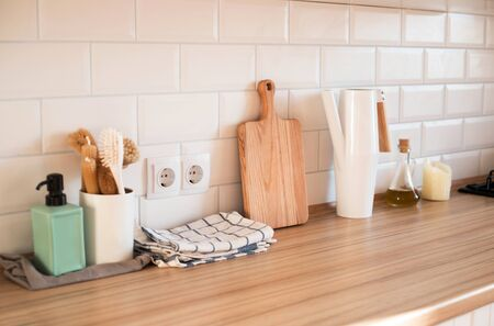 Interior details of light modern kitchen with brushes, towels and chopping board.